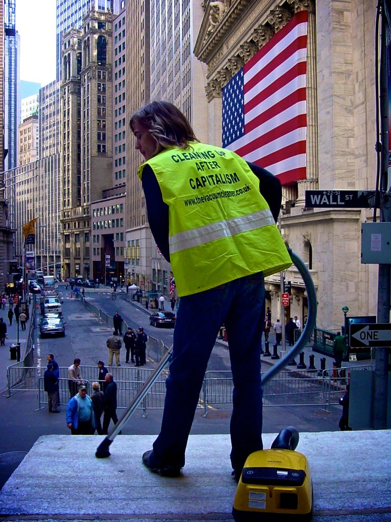 "a man wearing a hi vis vest with ""cleaning up after capitalism"" printed on the back, is vacuuming in Wall Street"