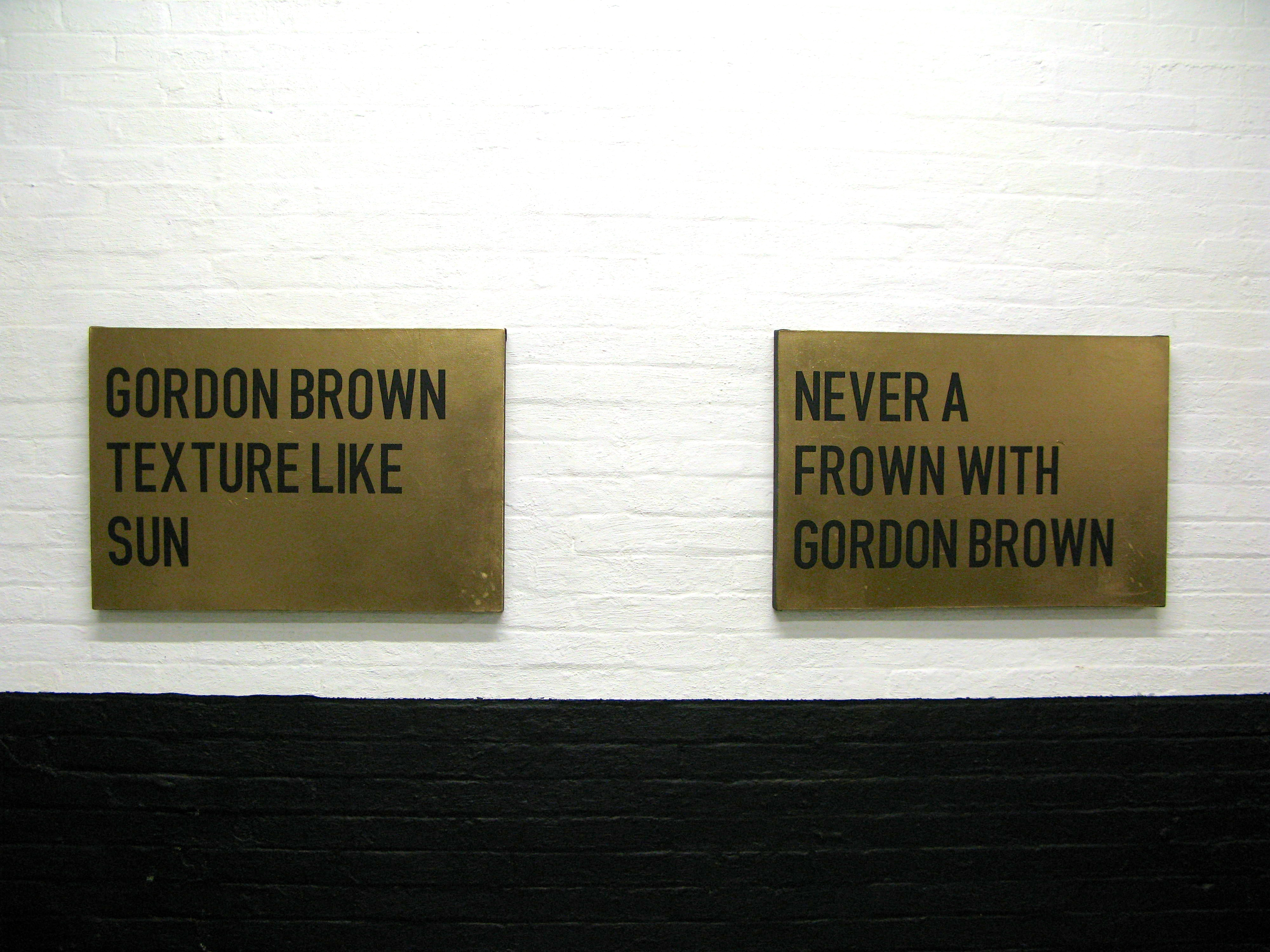 "two gold paintings with black text, one reads ""Gordon Brown texture like sun"" the other ""never a frown with Gordon Brown"""