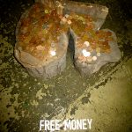 "a large up ended log with coins all over the top and the words ""free money"" written on the floor beneath it"