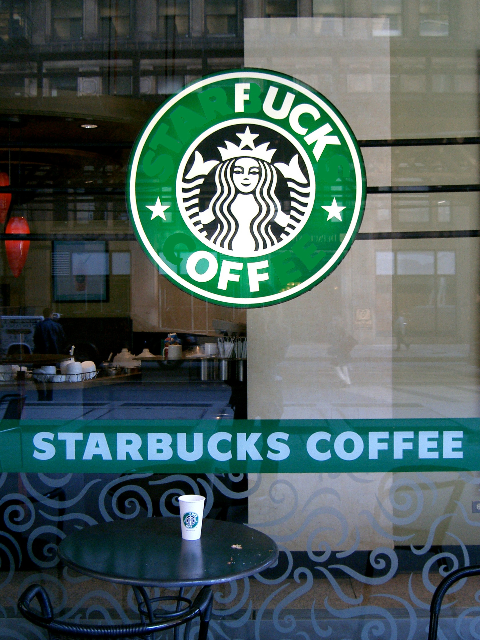 the front glass window of a Starbucks coffee shop with adapted logo to read 'fuck off'