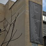 a large black banner hanging on a tall brick building displaying a list civil disobedience forms