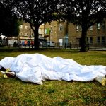A white duvet on the grass in a park with a figure underneath, gold feet stick out and a gold hand clutching a message in a bottle