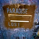 The outside of a letterbox which has been spray painted gold with the words 'paradise lost' stencilled out