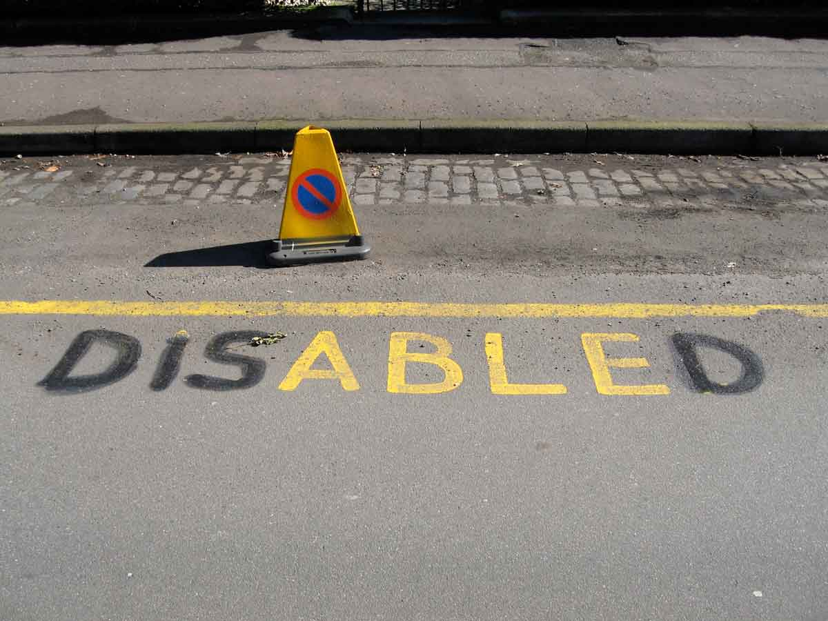 yellow disabled parking sign with the letters D I S D blacked out so that ABLE reads in yellow