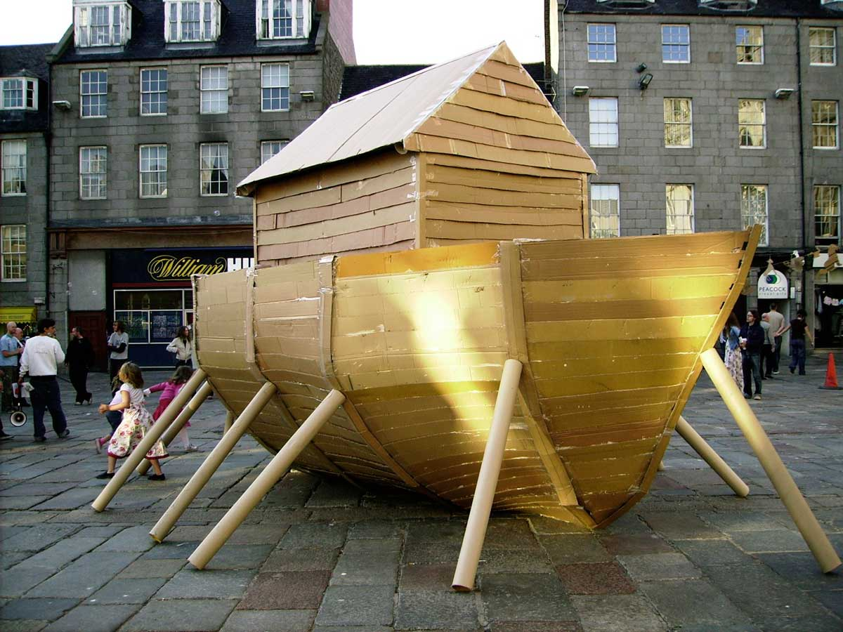 a boat made of cardboard outside on a paved area in front of some shops