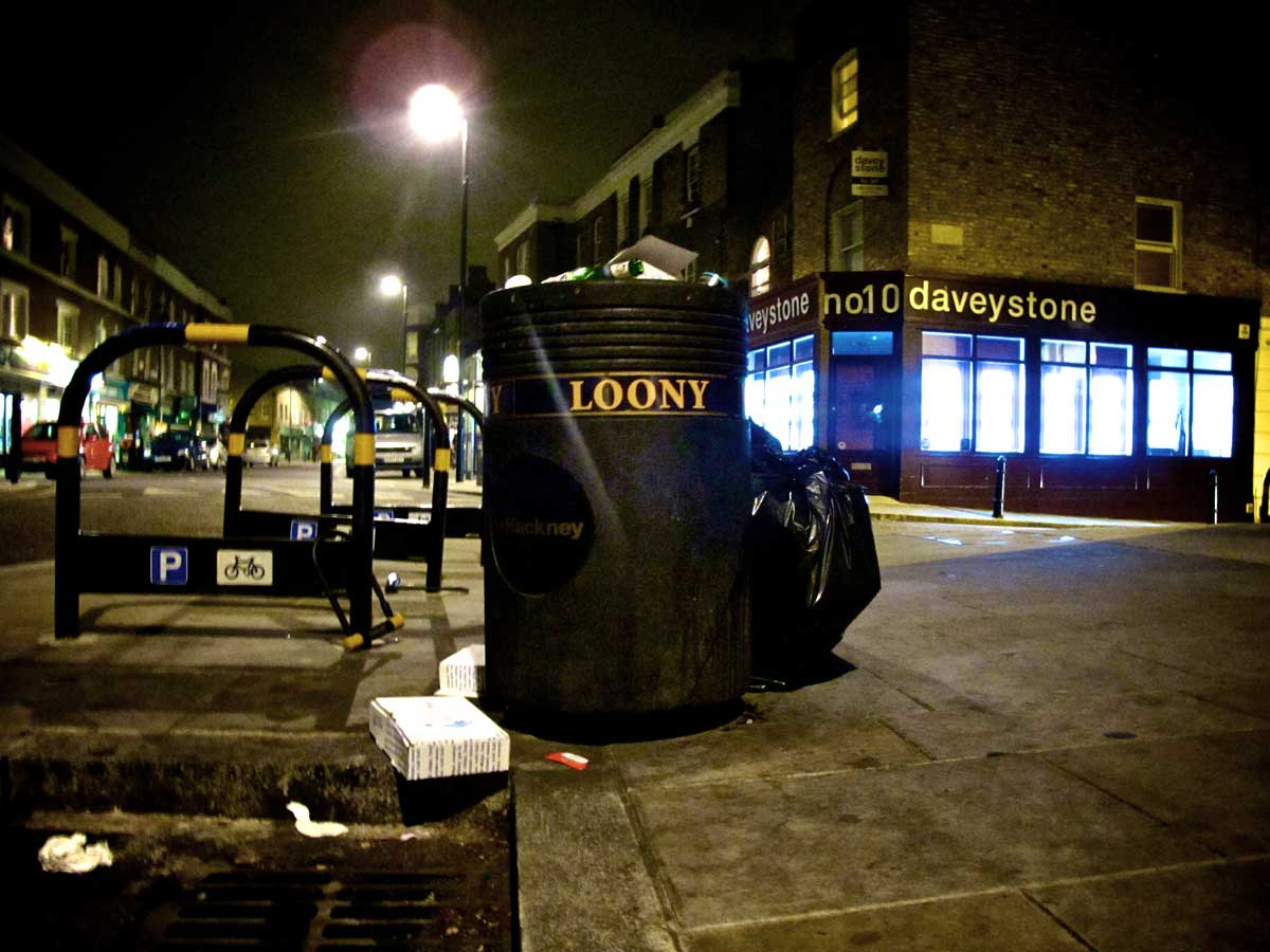 "a black street bin with ""loony"" written on it"