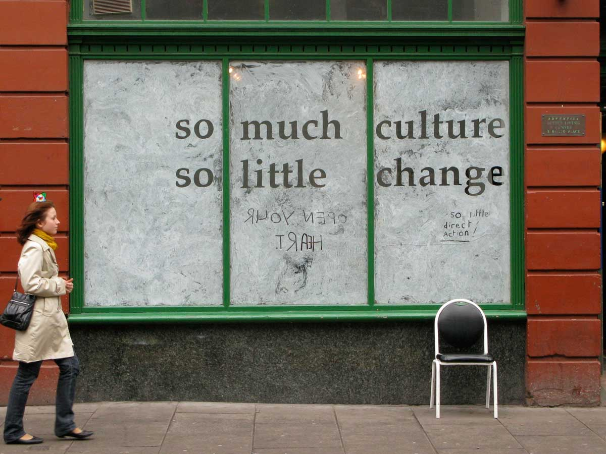 whitewashed shop window with the words 'so much culture so little change' exposed