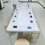 a long white table with different coloured and smelling soaps laid out on it