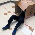Childs legs sticking out of a large cardboard box on the floor surrounded by art materials