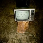 "an old television on top of an up ended log with the words ""I saw it on tv, so it must be true"" written onto the screen"