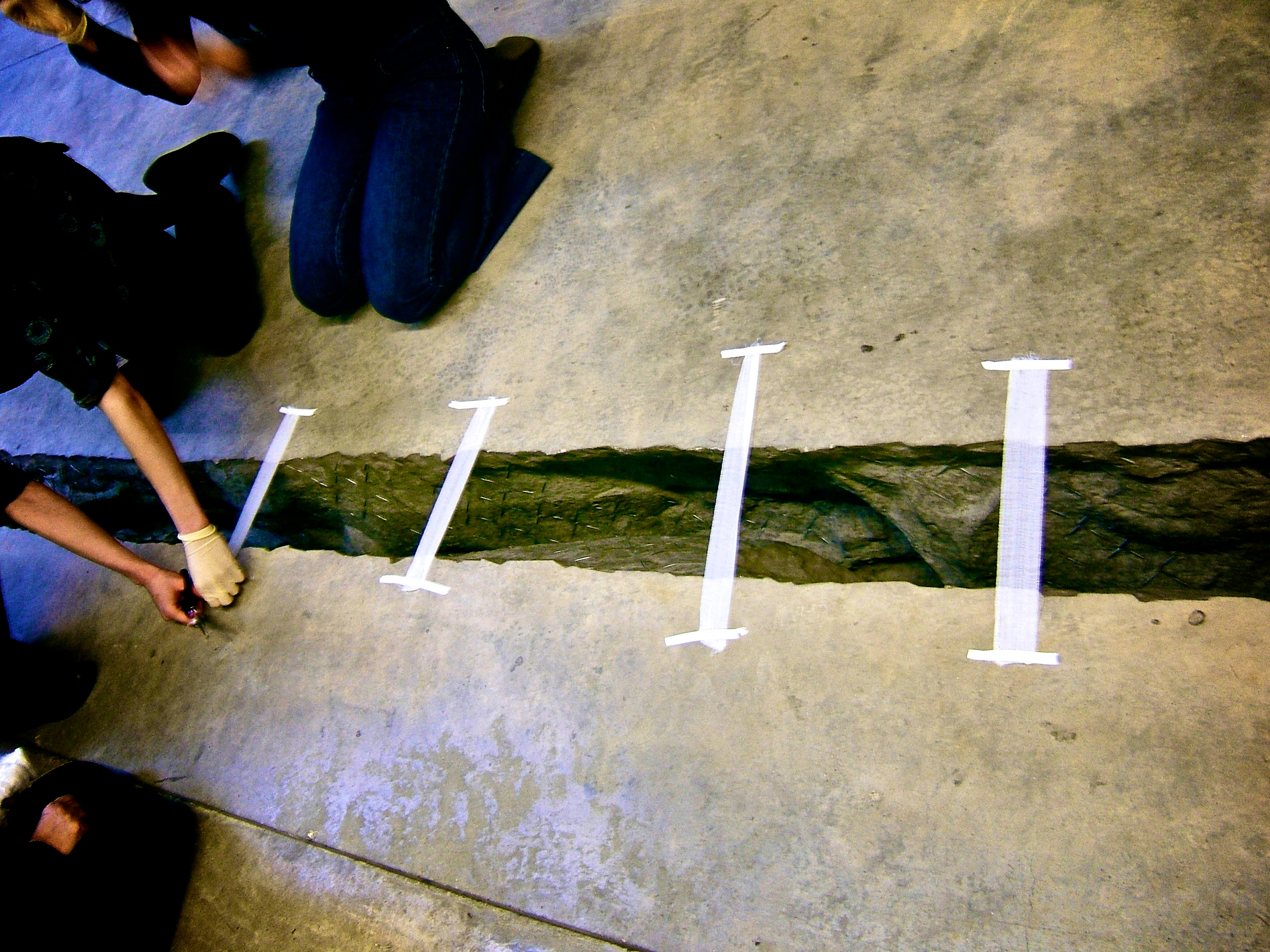 pieces of white tape stuck across a large crack in a concrete floor