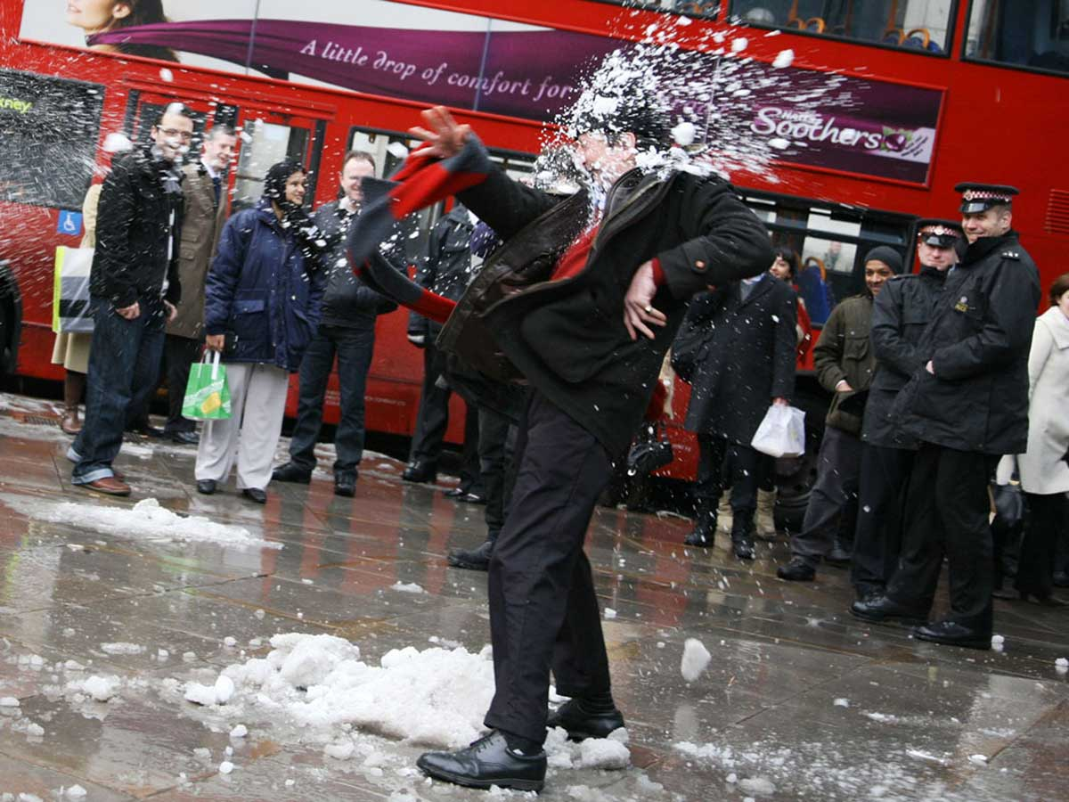 a man in a suit being hit in the face with a snowball