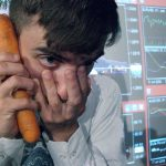 a man holding his hand to his face and a carrot to his ear like a telephone in front of stock market screens