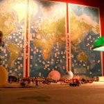 a world map wall with pieces of paper pinned to it and toys on a table in front of it