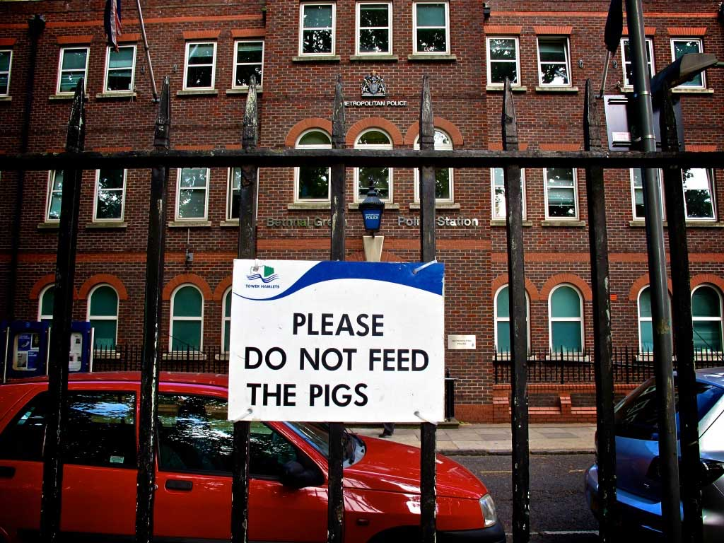 Towera sign on railings opposite a police station altered to read 'Please Do Not Feed the Pigs'