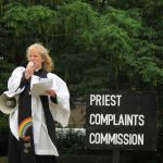 female priest with loud hailer standing next to a sign that says 'Priest complaints commission'