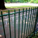 8 small string nooses hang from in between green park railings