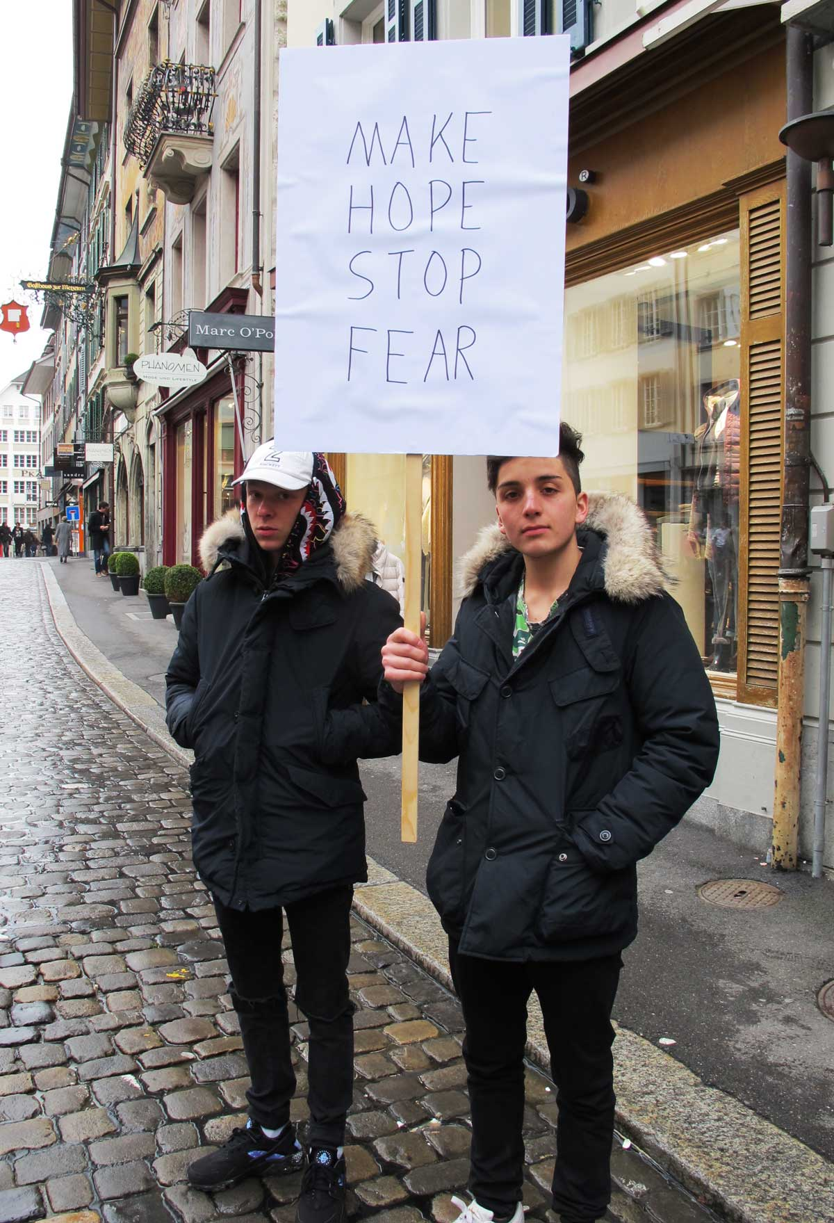 two boys hold a placard saying Make Hope Stop Fear