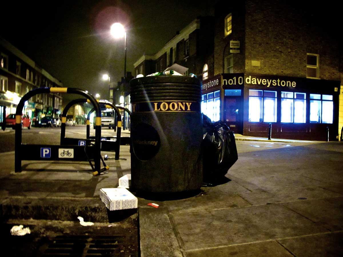 """a black street bin with """"loony"""" written on it"""