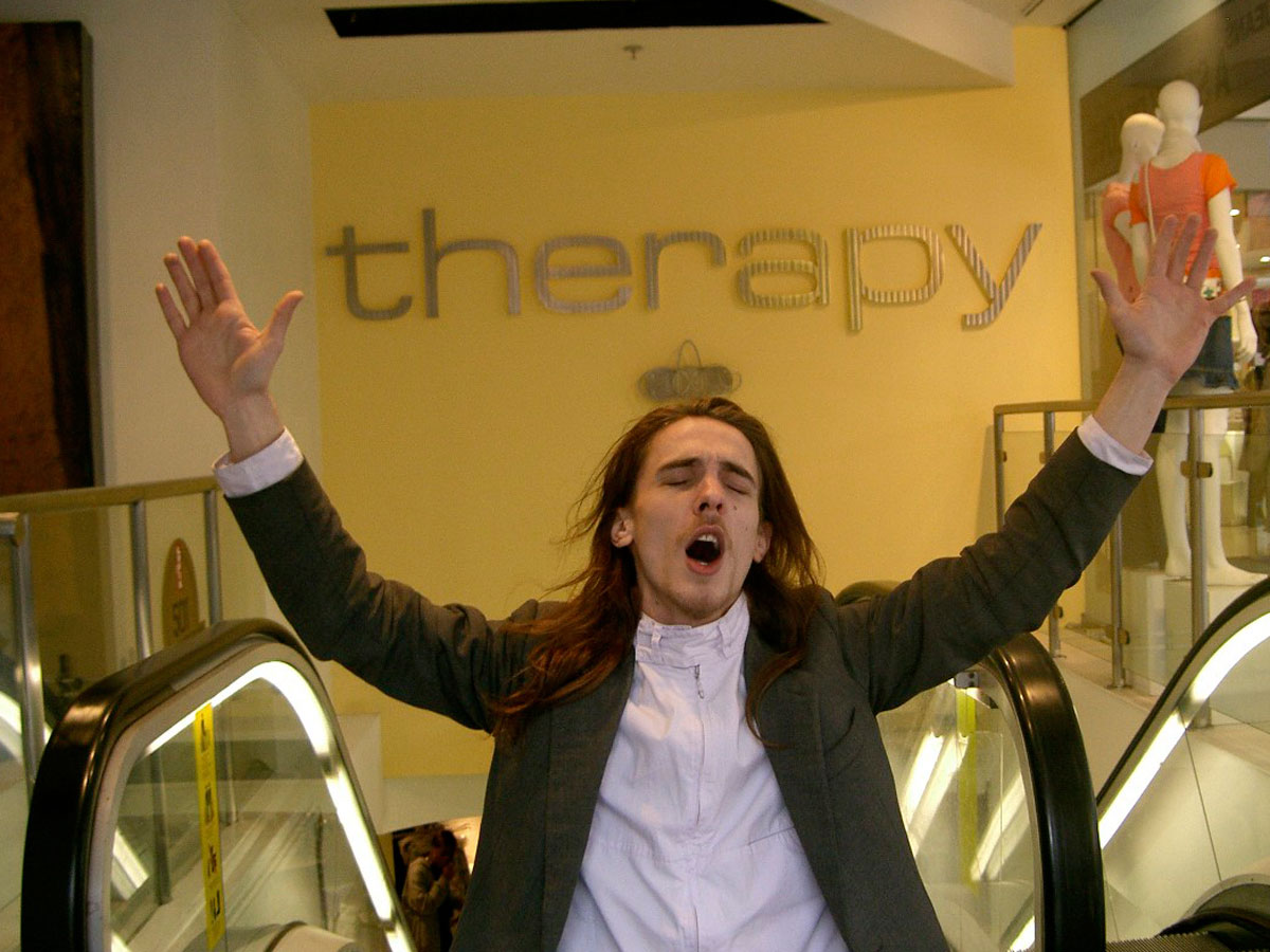 a white man with long hair at the top of an escalator with his arms raised