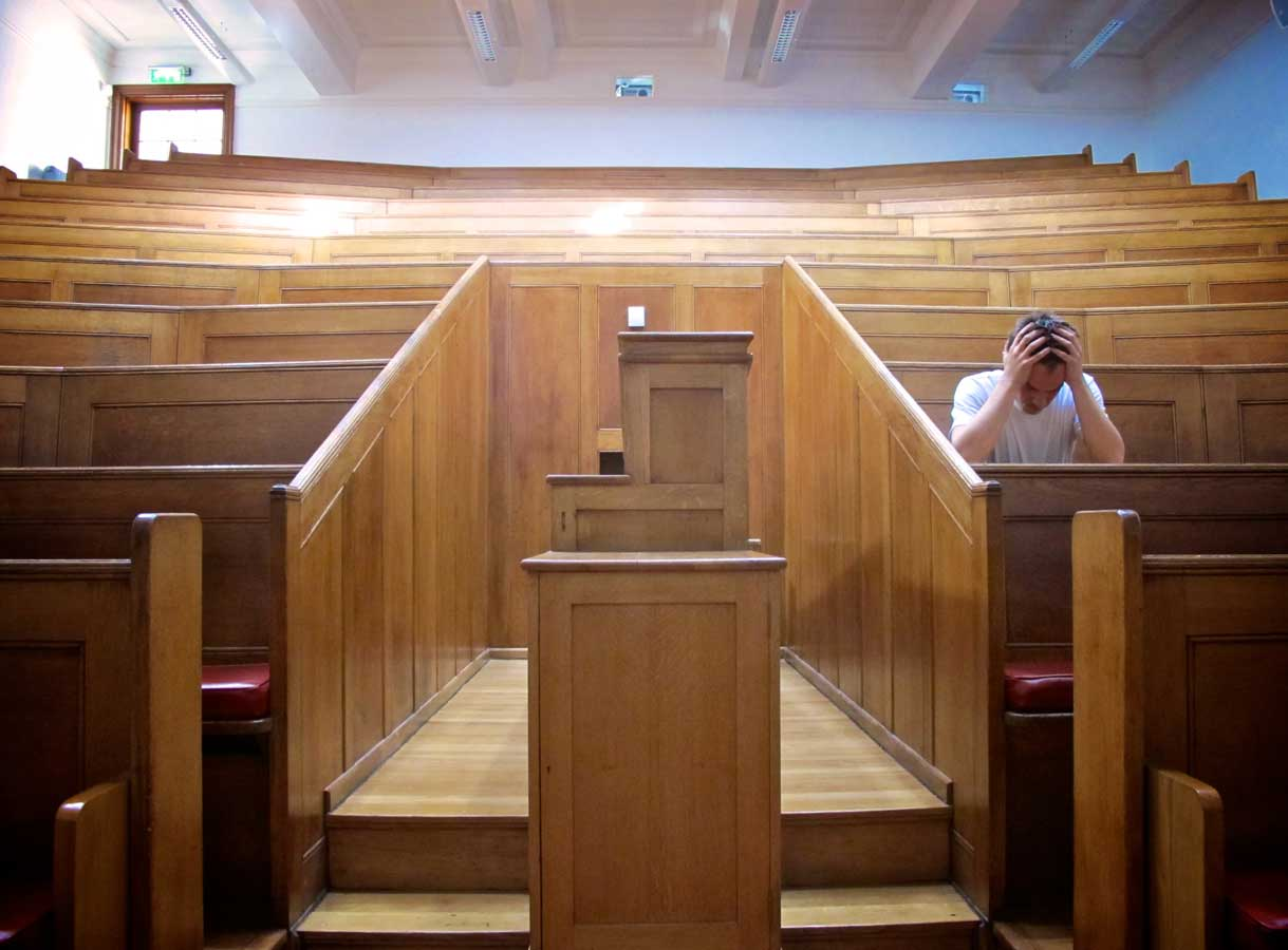 looking out from a lectern in a lecture hall a man sits on the right with his head in his hands