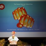 man in drag at a lectern on stage in front of a large projection of two fists spelling 'Take Care' on the fingers