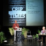 """man standing at a lectern and woman in a wheelchair at a table on stage with a projection behind reading """"Crip Times"""""""