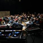 an audience sitting in a darkened room with dj and sound equipment