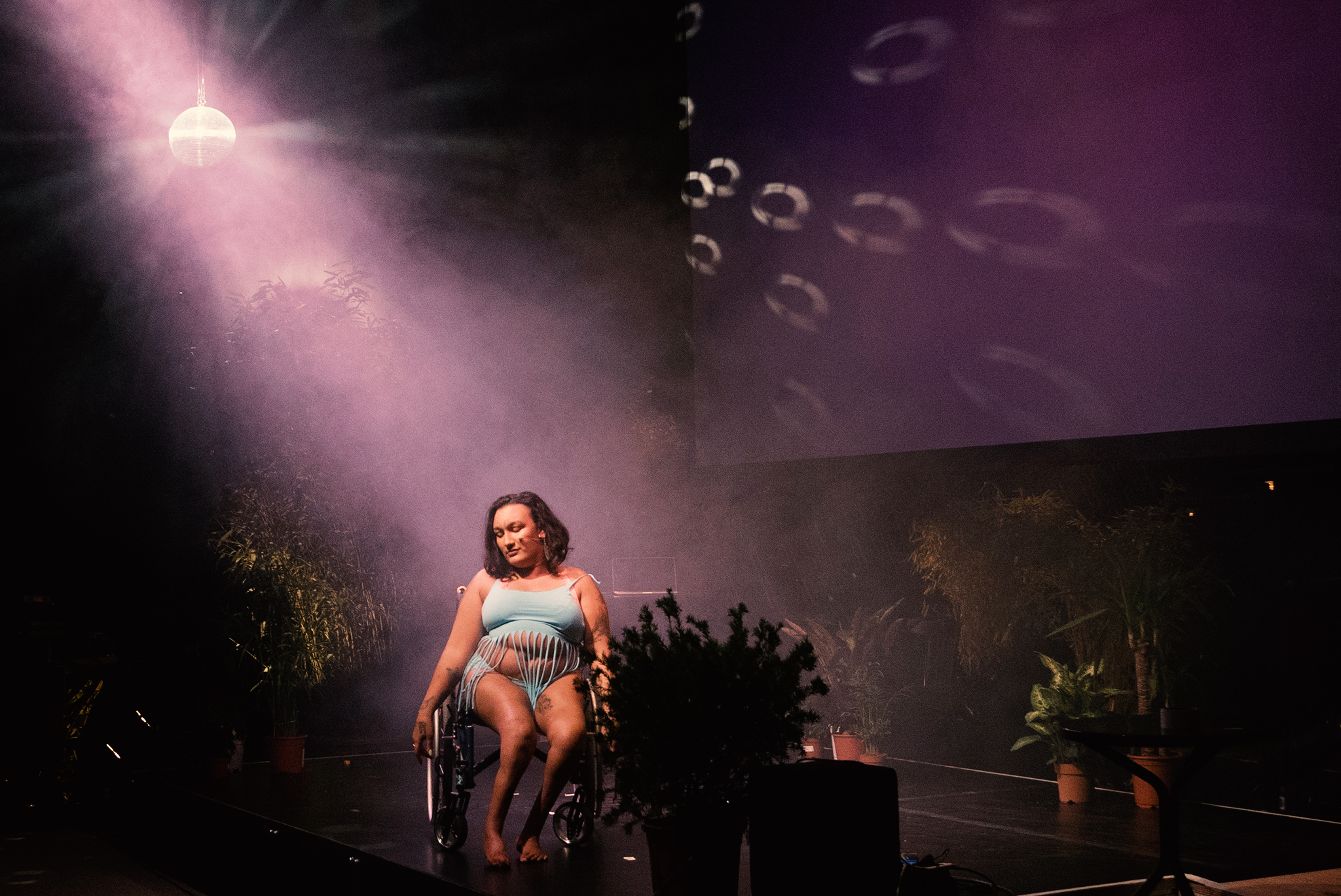 woman sitting in wheelchair on stage with pink lighting