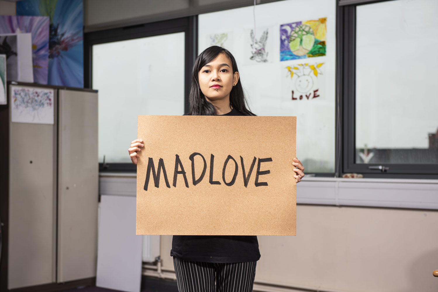 Madlove poster held by Hana Madness